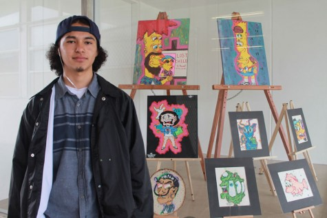 Humberto Juarez, a senior, stands near his art exhibit outside Room 92.