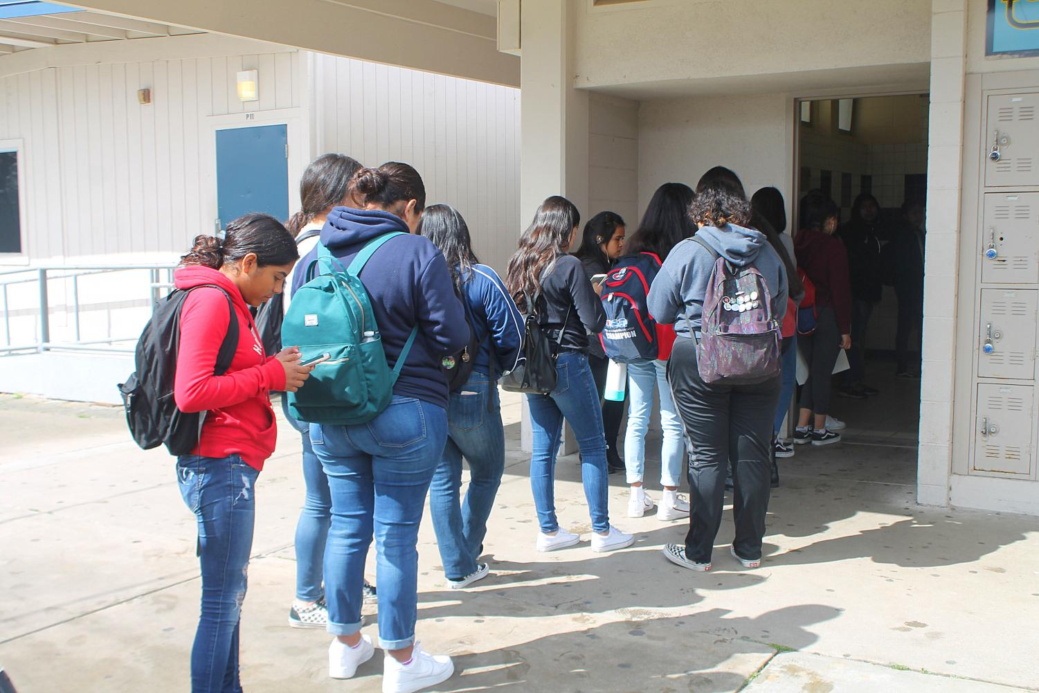 A line forms outside of the girls' restroom